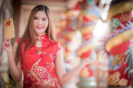 Asian woman in chinese dress holding couplet Lucrative  (Chinese word) with chinese temple background.