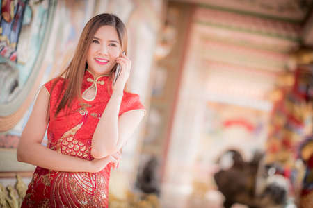 Asian Chinese woman in Traditional Chinese and hold telephone,by background ambience China ..