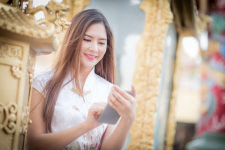 celebrate year: Asian Chinese woman in Traditional Chinese and hold telephone,by background ambience China . Stock Photo
