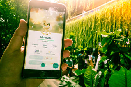 real world: BANGKOK, THAILAND - August 12,2016: Pokemon Go mobile game app on smart phone gadget with play screen catching cartoon in real world using gps technology ,Lighting with sun flare