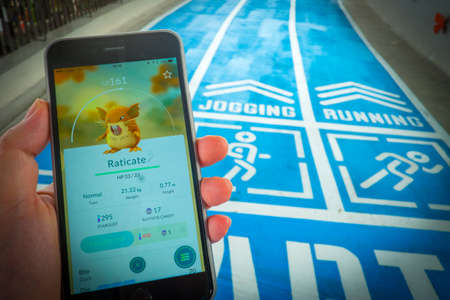 nintendo: BANGKOK, THAILAND - August 12,2016:Apple iPhone5s held in one hand showing its screen with Pokemon Go application. Editorial