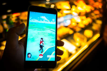 BANGKOK, THAILAND - August 12,2016: Pokemon Go gameplay screenshot on the phone. Pokemon Go is a location-based augmented reality mobile game,Playing in cafe