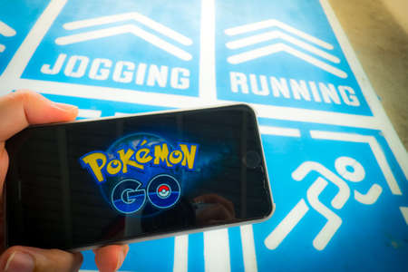 nintendo: BANGKOK, THAILAND - August 12,2016: Pokemon Go is a free-to-play, GPS based augmented reality mobile game developed by Niantic for iOS and Android devices ,Lighting with sun flare Editorial