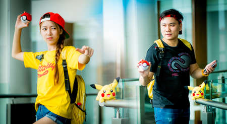 BANGKOK, THAILAND - August 14,2016:  Trainer boy  playing pokemon , pokemon ball and mobile pokemon go game app on smart phone gadget ,Lighting with sun flare