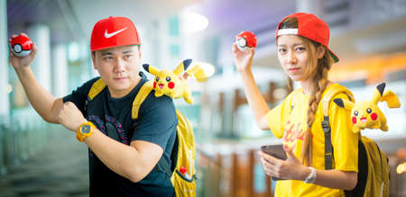 BANGKOK, THAILAND - August 14,2016: Trainer boy playing pokemon , pokemon ball and mobile pokemon go game app on smart phone gadget ,Lighting with sun flare Editorial
