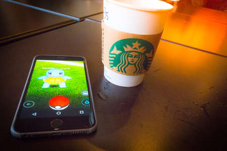 screenshot: BANGKOK, THAILAND - August 12,2016: Pokemon Go gameplay screenshot on the phone. Pokemon Go is a location-based augmented reality mobile game,Playing in cafe