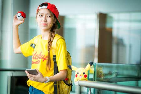 nintendo: BANGKOK, THAILAND - August 14,2016:  Trainer girl playing pokemon , pokemon ball and mobile pokemon go game app on smart phone gadget ,Lighting with sun flare