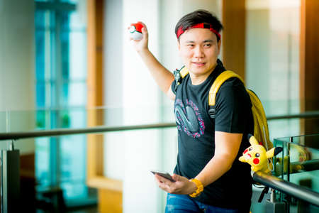 rubik: BANGKOK, THAILAND - August 14,2016:  Trainer boy  playing pokemon , pokemon ball and mobile pokemon go game app on smart phone gadget ,Lighting with sun flare