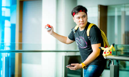 nintendo: BANGKOK, THAILAND - August 14,2016:  Trainer boy  playing pokemon , pokemon ball and mobile pokemon go game app on smart phone gadget ,Lighting with sun flare