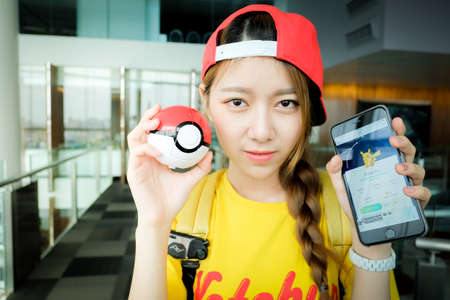 nintendo: BANGKOK, THAILAND - August 14,2016: Trainer girl playing Apple iPhone5s held in one hand showing its screen with Pokemon Go application,Lighting with sun flare