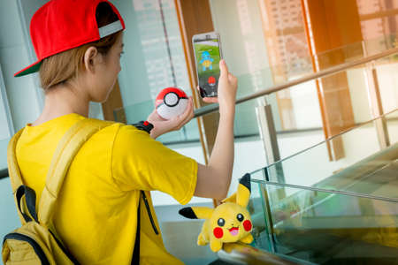 real world: BANGKOK, THAILAND - August 14,2016:  Trainer girl playing pokemon , pokemon ball and Pokemon Go mobile game app on smart phone gadget with play screen catching cartoon in real world using gps technology ,Lighting with sun flare