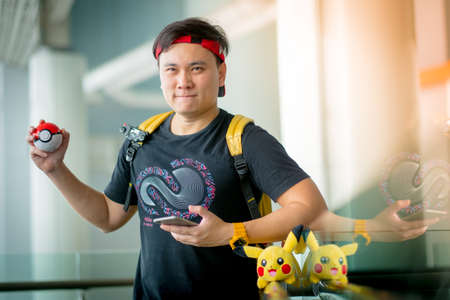 nintendo: BANGKOK, THAILAND - August 14,2016:  Trainer boy playing pokemon , pokemon ball and mobile pokemon go game app on smart phone gadget ,Lighting with sun flare Editorial