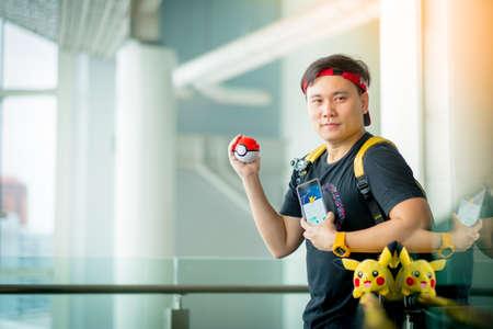 gameplay: BANGKOK, THAILAND – August 14,2016:  Trainer boy playing pokemon , pokemon ball and Pokemon Go gameplay screenshot on the phone ,Lighting with sun flare
