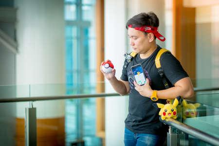 gameplay: BANGKOK, THAILAND - August 14,2016:  Trainer boy playing pokemon , pokemon ball and Pokemon Go gameplay screenshot on the phone ,Lighting with sun flare Editorial