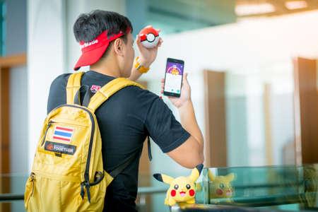 screenshot: BANGKOK, THAILAND - August 14,2016:  Trainer boy playing pokemon , pokemon ball and Pokemon Go gameplay screenshot on the phone ,Lighting with sun flare Editorial