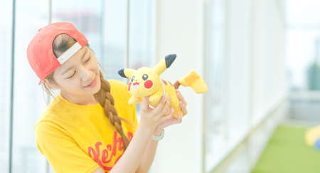 nintendo: BANGKOK, THAILAND - August 14,2016:  Trainer girl playing pokemon , pokemon ball ,Lighting with sun flare