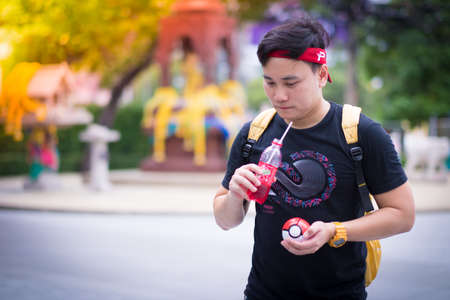 rubik: BANGKOK, THAILAND - August 14,2016:  Trainer boy playing pokemon , pokemon ball And are wondering why pokemonstop in a drinking water well  ,Lighting with sun flare
