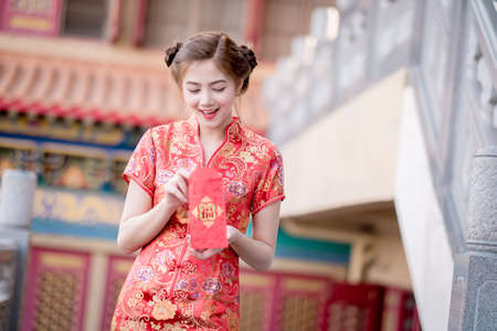 blessing: Asian woman in chinese dress holding couplet Happy  (Chinese blessing word) with chinese temple background.