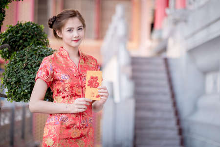 other keywords: Asian woman in chinese dress holding couplet Happy  (Chinese blessing word) with chinese temple background.