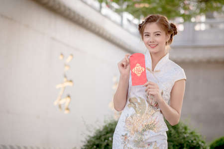 blessing: Asian woman in chinese dress holding couplet Happy  (Chinese blessing word) with chinese temple background. word) with chinese temple background.