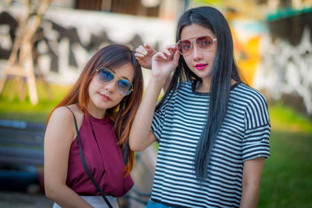 Two teenage girls friends in hipster outfit.at the park outdoors make selfie on a phone And fashion sunglasses.