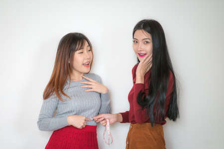 calibrate: Two women are on a diet is to measure the levels of the waist to each other with tape centimeter