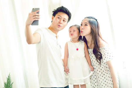Family with little girl in park taking selfie by mobile phone. Backlit shot
