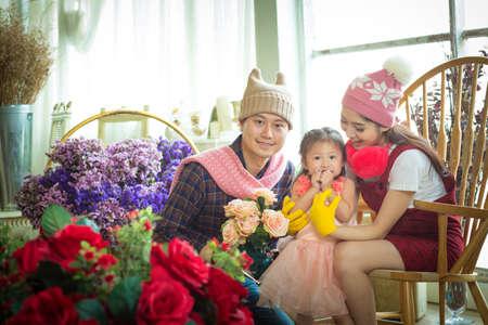 Family with little girl in garden. Backlit shot Stock Photo