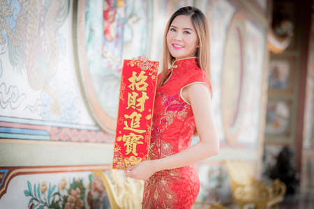 Asian woman in chinese dress holding couplet strong  (Chinese blessing word) with chinese temple background.