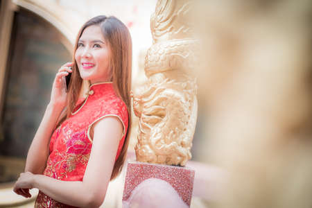 ambience: Asian Chinese woman in Traditional Chinese and hold telephone,by background ambience China ..