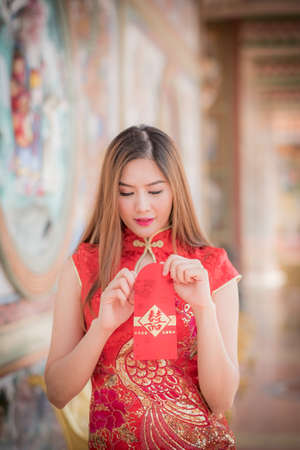 Asian woman in chinese dress holding couplet Happy  (Chinese word) with chinese temple background.