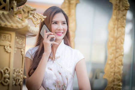 ambience: Asian Chinese woman in Traditional Chinese and hold telephone,by background ambience China . Stock Photo