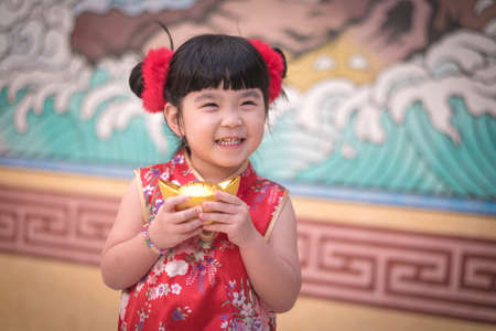 China girl in traditional Chinese dress greeting, holding a gold ingot standing,Photos provided by background ambience China . Stock Photo