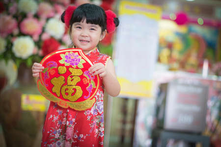Asian girl  in chinese dress holding couplet Happy  (Chinese word) with chinese temple background.