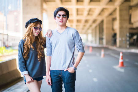 beautiful womb: Couple standing pose . And sunglasses , Background road under the highway . Stock Photo