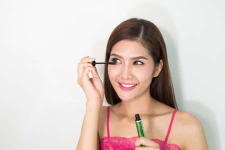 beautiful womb: Beauty makeup woman putting mascara eye make up on eyes. Asian fresh face girl looking in the mirror looking at camera isolated on white background. Mixed race ethnic Asian Chinese  Caucasian model. Stock Photo