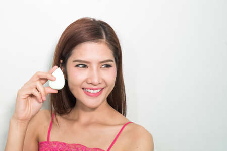 beautiful womb: Beautiful young woman applying foundation to face with green egg sponge. Isolated over white backgound. Copy space.