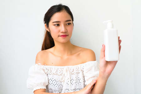 doctor holding gift: Body lotion Portrait of Beautiful  Woman looking at Camera. Beautiful Asian female model on Whitebackground with clipping path.