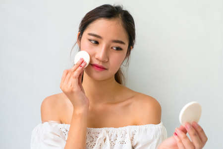 beautiful womb: Young woman applying foundation on face with powder puff, skin care concept