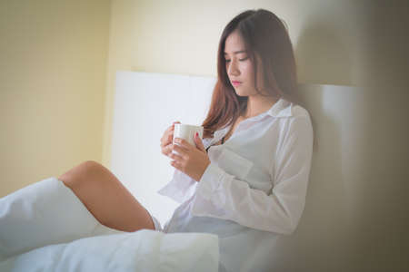 Beautiful brunette woman drinking and morning coffee in bedroom ,Lighting with sun flare Stock Photo