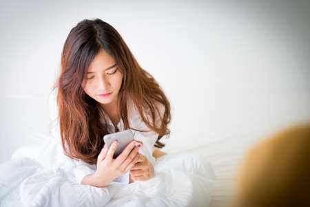 home lighting: girl using a mobile phone lying on the bed at home,Lighting with sun flare