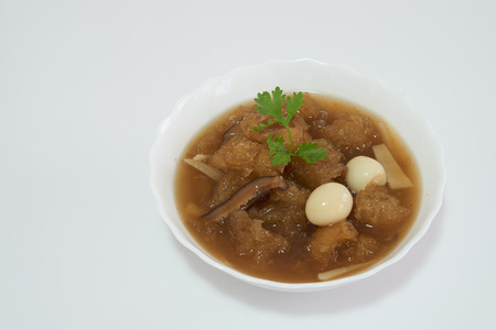 red braised: Chinese style soup or braised fish maw in red gravy with eggs, mushroom, and bamboo shoot in white bowl. Top view. Isolated on white background.