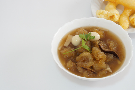 maw: Chinese style soup or braised fish maw in red gravy with eggs, mushroom, and bamboo shoot in white bowl (put in front of dried fish maw) on white background. Copy space on the left. Stock Photo