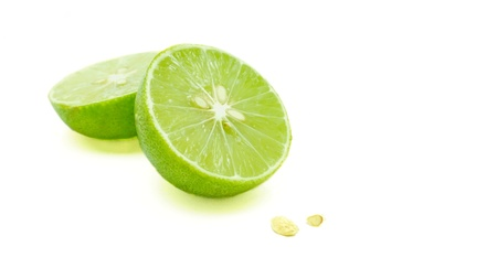 Two halves of splitted green lime with seeds on white background. A kind of fruit used as an ingredient for cooking, especially in sour food. Scientific name - Citrus x aurantiifolia