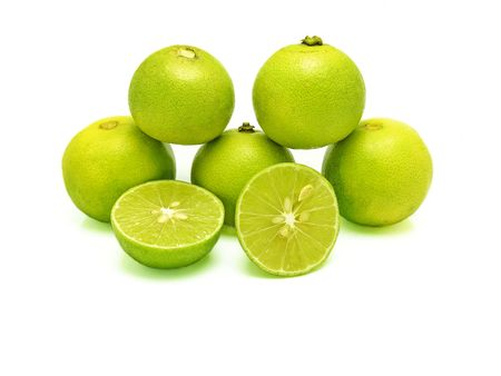 Five green limes (in pyramid stacking) and two splitted halves on white background. A kind of fruit used as an ingredient for cooking, especially in sour food. Scientific name - Citrus x aurantiifolia Stock Photo