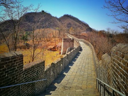 Ancient pavement of China Great Wall and trees in autumn. It is the most eastern part of the Great Wall and located on Hushan or Tiger mountain, Dandong city, Liaoning province; near China-North Korea border.