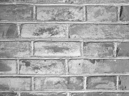 Texture of old blocks on cement wall; black and white color; untidy masonry; use uneven sizes of grey concrete bricks. An example of use limited resources economically.