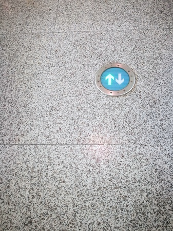 Green arrows sign on granite floor in public transport station or airport passenger terminal. There are copy-space on the left and below of image. Banco de Imagens