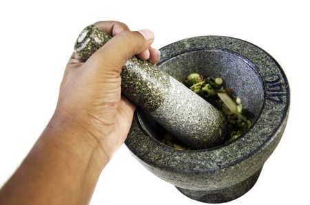 Hands are pounding spices in a mortar stone Stock Photo