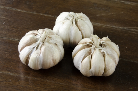 Garlic with a wooden floor backdrop.